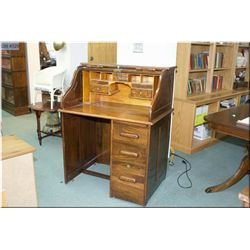 A vintage single pedestal S-curve roll top desk with fitted interior