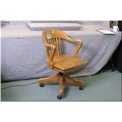 An oak swivel office chair on castors