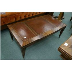 Antique flame mahogany coffee table with inset leather top and original castors