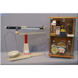 A selection of vintage apothecary bottles in small display plus a balance scale etc.