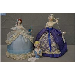 Two vintage glazed bisque pin cushion dolls with decorative skirts and hat pins plus a glazed bisque