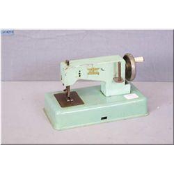 Vintage German made cast metal child's sewing machine with original label