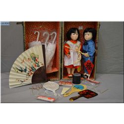 """A vintage doll case containing two vintage 13"""" Oriental dolls by Effanbee """"Little Tiger"""" and """"Orange"""