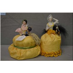 Two vintage pincushion dolls both with yellow silk skirts and hat pins