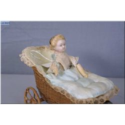 Antique pull toy, wax over papier-mƒch' doll in wicker buggy with articulated arms and crier, circa,