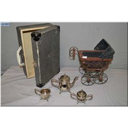 A vintage doll trunk, a small wooden doll carriage and a silver plate child's tea set