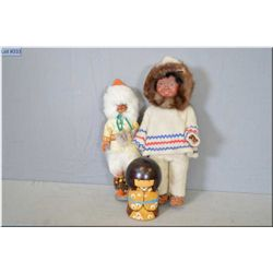 Three collectible dolls including vinyl and hard plastic Eskimo dolls and a wooden Japanese doll