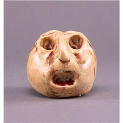 "Ceramic glazed sculpture of odd face, signed ""K""."