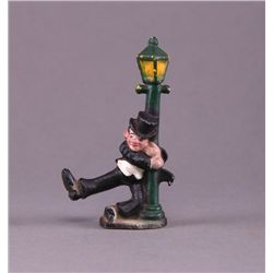 Hand painted cast iron figurine of man swinging on lamp