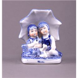 Dutch ceramic figurine of children under a umbrella.