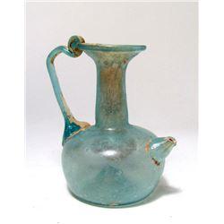 A Roman pale blue glass spouted vessel