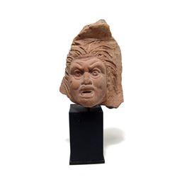 An Egyptian terracotta dramatic face