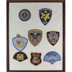 Framed collection of 8 law enforcement patches
