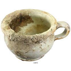Handled porcelain chamber-pot, intact and partially encrusted.