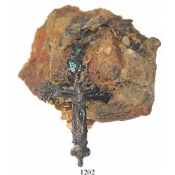 Brass cross with Jesus figure (complete) encrusted into piece of impacted debris.