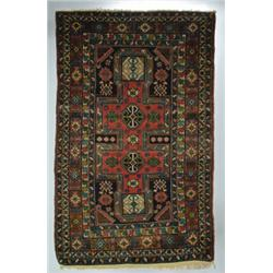A SHIRVAN RUG, Caucasian, early 20th century, a pale red double keyhole motif medallion on a navy...