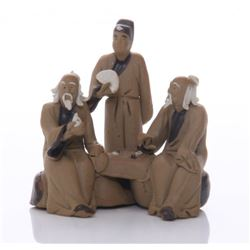 Early 20th Century mud men figurine of three men at a s