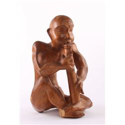 Indonesian wood sculpture carving of a man playing an i