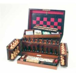 A late Victorian walnut games compendium, with swing doors and compartmented interior containing...
