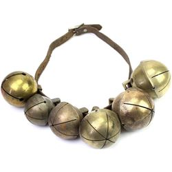 Collection of 6 sleigh bells of various sizes, brass and copper, on a leather strap.