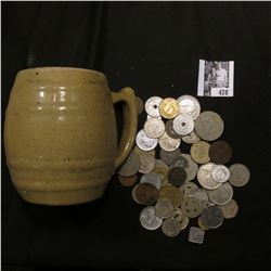 """Stoneware Mug """"Uhl Pottery Co. 16 Huntingburg Ind."""" with a large group of unsorted foreign coins and"""