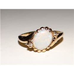 Australian Fire Opal ladies ring with 2 small White Spinel, in 10 kt yellow gold, size