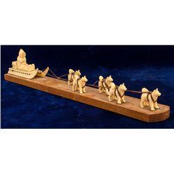 Ivory Dog Team Pulling Sled
