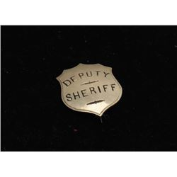 Vintage shield badge marked Deputy Sheriff with sticker on back