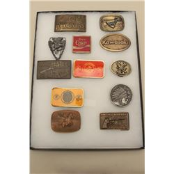 Belt buckle collection in display case. Coke (Enameled), guns, and