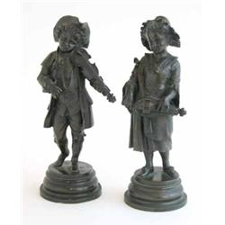 A pair of French bronze figures, of a young boy playing the
