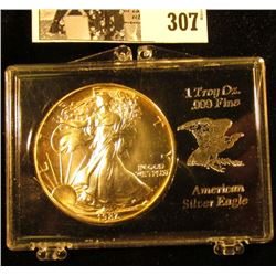 1987 U.S. American Eagle Silver Dollar, lightly toned Gem BU in a special plastic case.