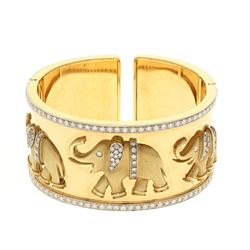 BRACELET: [1] 18 karat yellow and white gold hinged cuff style bangle bracelet with elephants and se