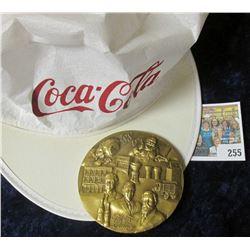 """Coca-Cola"" Advertising cap; & 1886-1986 Coca-Cola Distributor Large Bronze Medal, 3"" x 1/4"", depict"