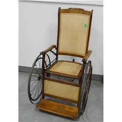 Vintage wood framed wheel chair, cane seat and back