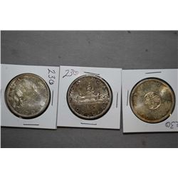 Three Canadian silver dollars including a 1964 and two 1965