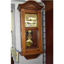 Semi contemporary chiming wall clock with attached ormolu style decorative face and visible brass pe