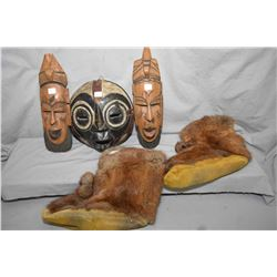 Three carved masks and a pair of leather and fur mukluks