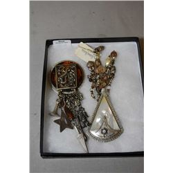 Two vintage David Navarro brooches including mother-of-pearl with hanging beads and a tortoise shell