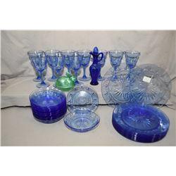 Two trays of Avon blue glass including ten goblets, one cruet, ten dinner plates, twelve cereal bowl