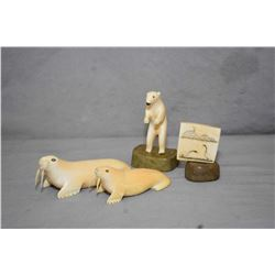 Four Inuit carvings including two tusk walrus, scrimshaw on a stand and a standing bear on a soapsto