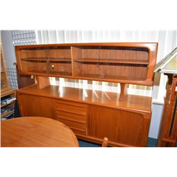 Mid century unmarked teak sideboard with four center drawers, flanked by two wrap around rolled door