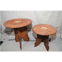 Two carved Indonesian folding tables with fret work bases and inlaid bone and carved tops