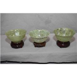 "Three carved jade bowls on rosewood bases, each approximately 2 1/4"" in height and 4 3/4"" in diamete"