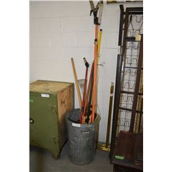 Galvanized garbage can containing gardening tools including hoe, extension poles etc.