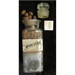 """Large 10"""" x 3 1/4 Apothcary Jar with glass Stopper, some contents included.  Labeled """"Myristica"""".  A"""