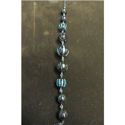 A LARGE BALL OF FUN IS STUDDED WITH DAZZLING BLUE CRYSTALS SET IN BLACK HEMATITE AND FANCY DESIGNER