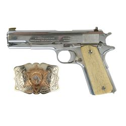 "Brad Johnson's Colt 1911 .45 pistol with engraved commemorative ""Honorary Sheriff"" belt buckle."