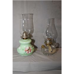 Two vintage glass oil lamps including colourless and jade glass with floral motif, both with hurrica