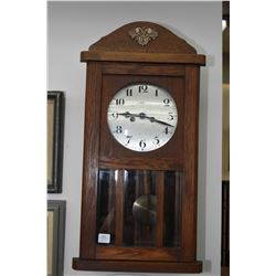 Oak striking wall clock with visible pendulum in bevelled glass clock case