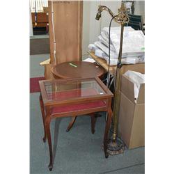 Table style display vitrine and a vintage brass bridge lamp